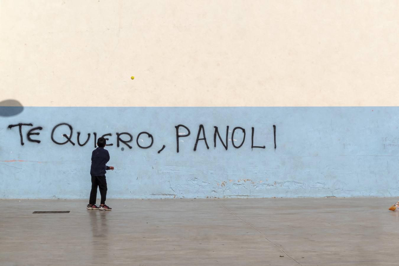 """Un niño juega con una pelota frente a una pared, en la que aparece escrita la frase """"Te quiero, Panoli"""""""