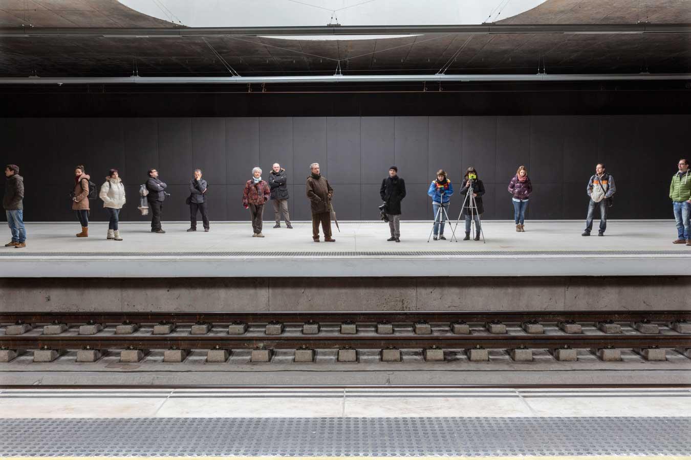 Pasajeros asomados al andén mientras esperan la llegada del tren