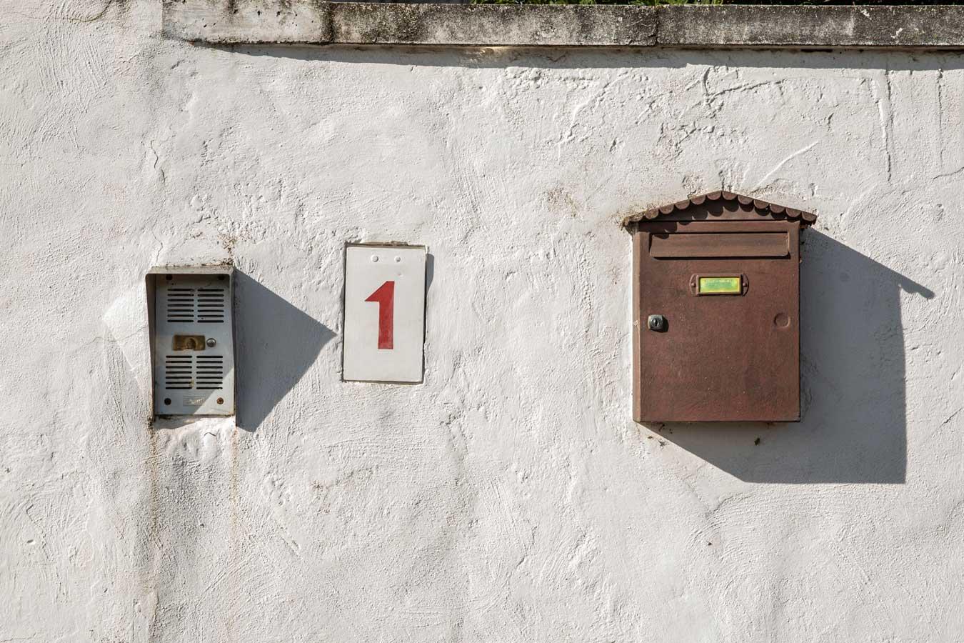 Imagen de una pared blanca, donde llama la atención la disposición de un timbre, el número del portal y un buzón de cartas.