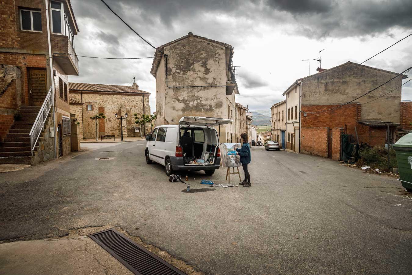 Una mujer pinta un cuadro en mitad de la calle de un pueblo