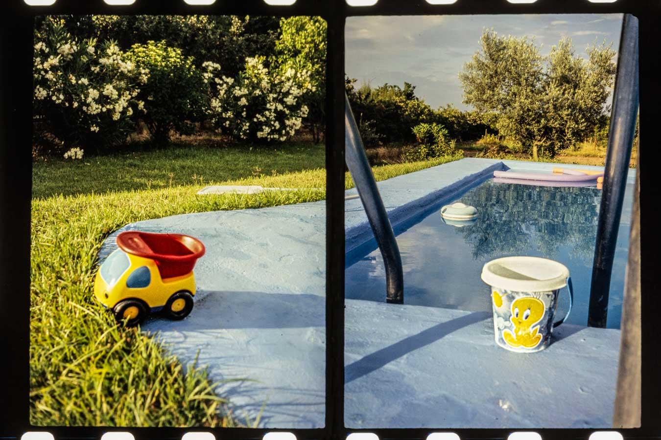 Imagen de una piscina con un camión de juguete y un cubo de playa junto al borde.