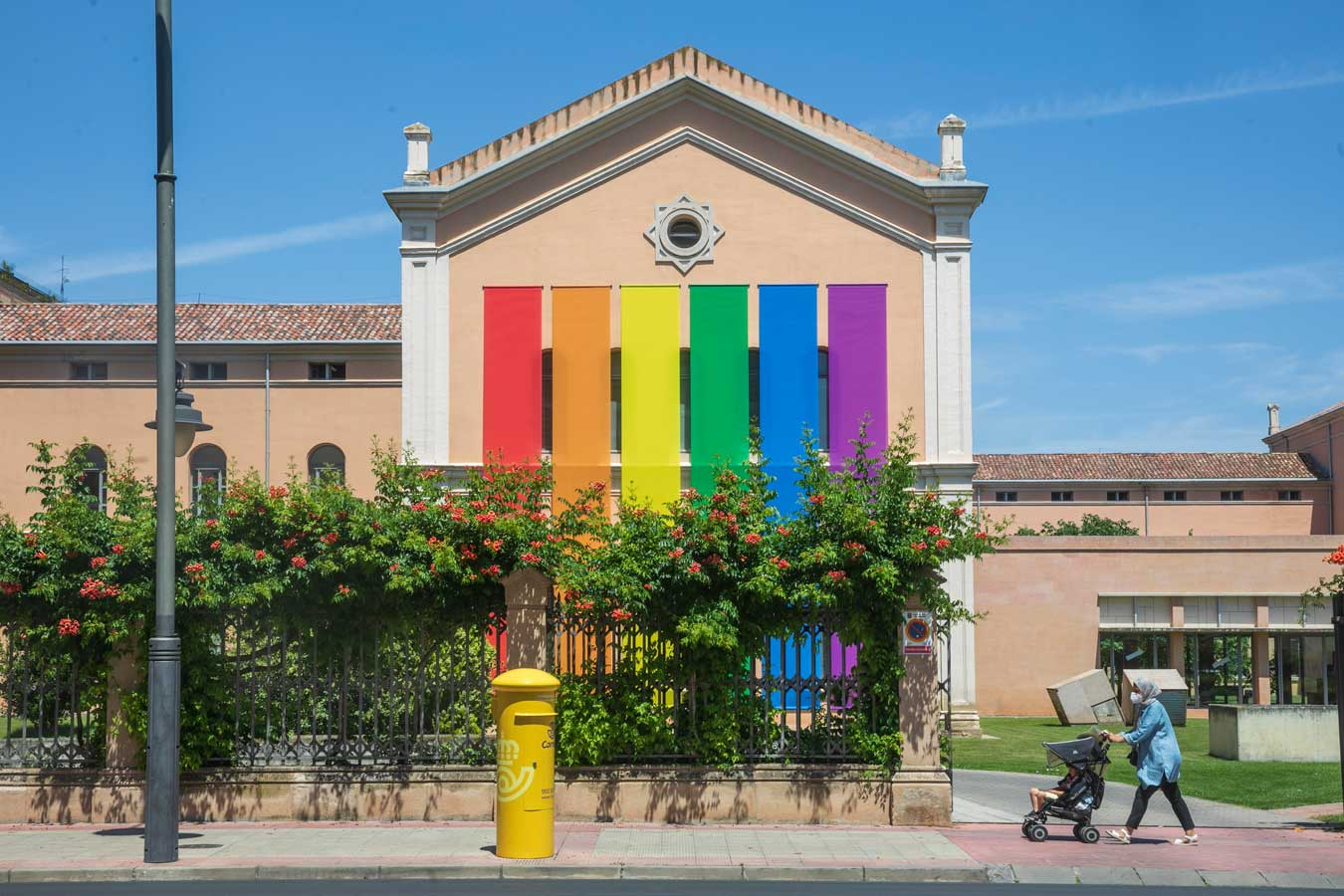 Fachada de un edificio donde se ve expuesta la bandera arcoiris LGTBI