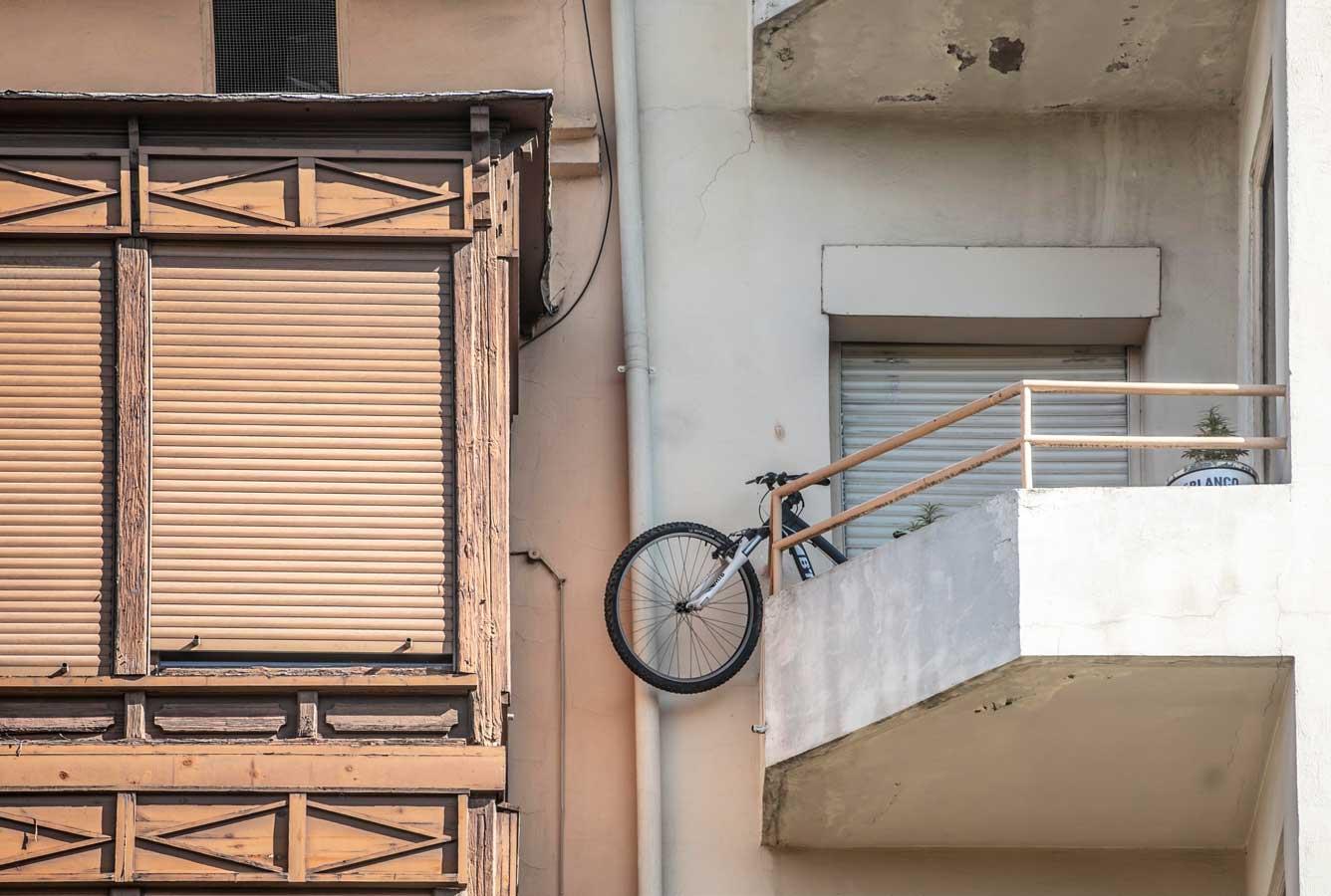 La rueda delantera de la bicicleta se asoma por el balcón, rebasando la barandilla. Como si fuera una vecina más del barrio. Pero una vecina todo terreno.