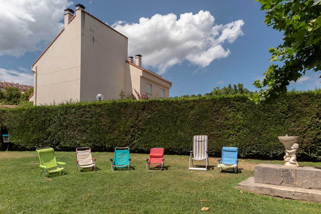 Imagen de varias tumbonas y sillas plegables colocadas en fila en el verdor de la piscina