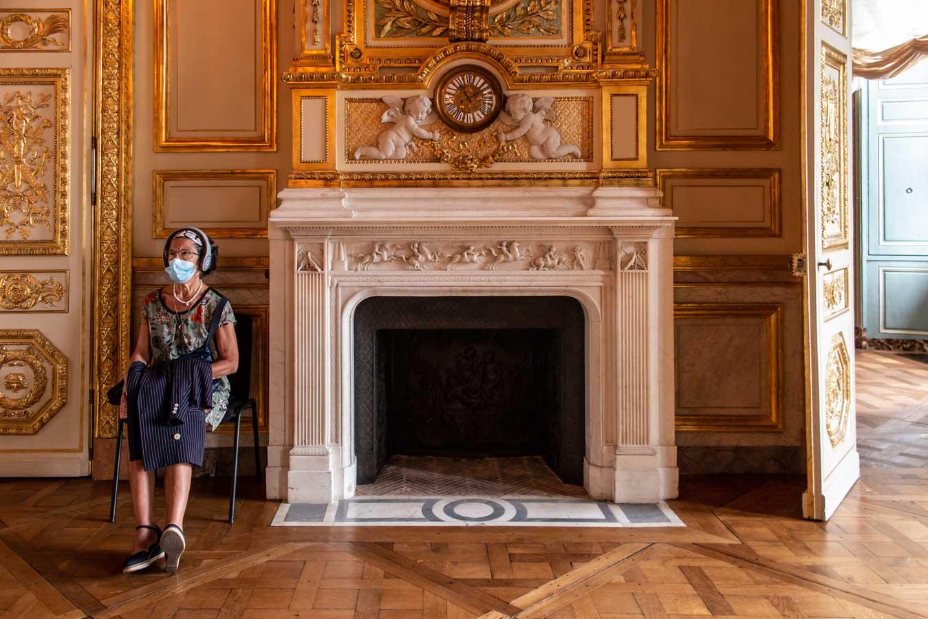 Una mujer sentada en una silla, junto a la chimenea del salón principal de un palacio